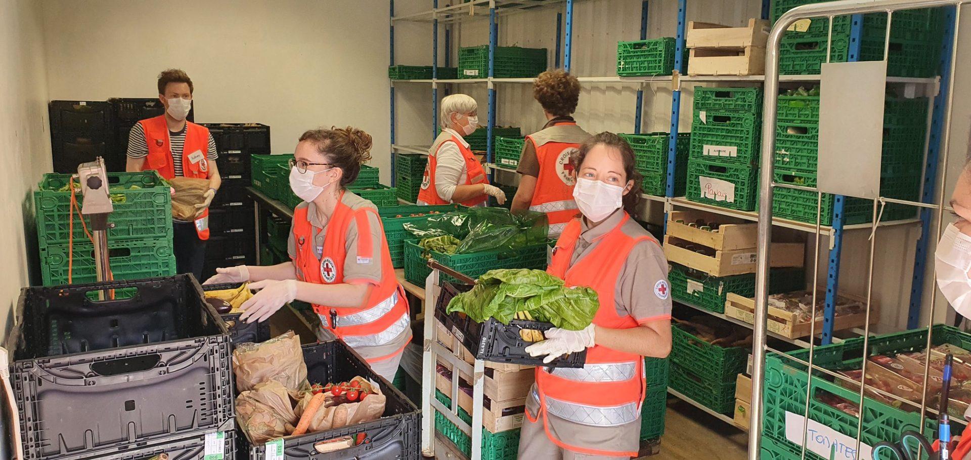5 Bénévoles de la Croix Rouge transportent des caisses dans un réserve de légumes frais