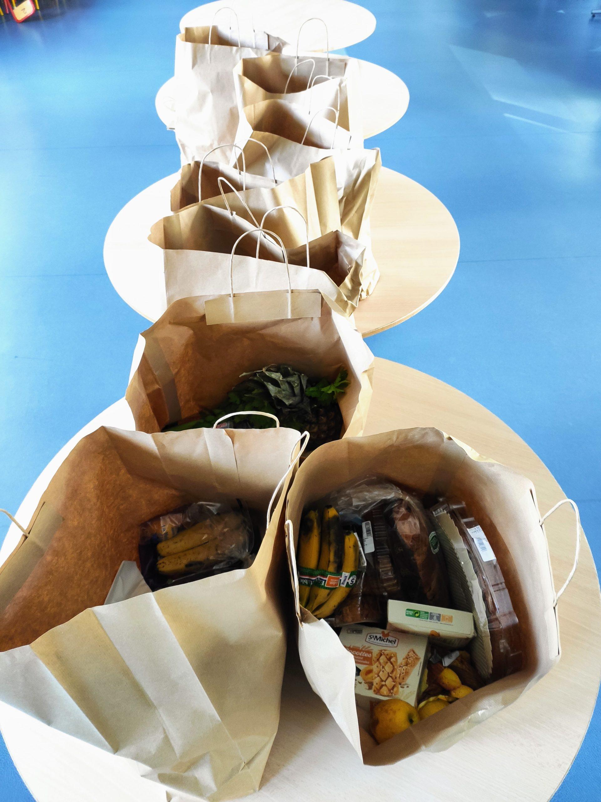 Sacs de course en papier ouvert avec des denrées alimentaires dedans