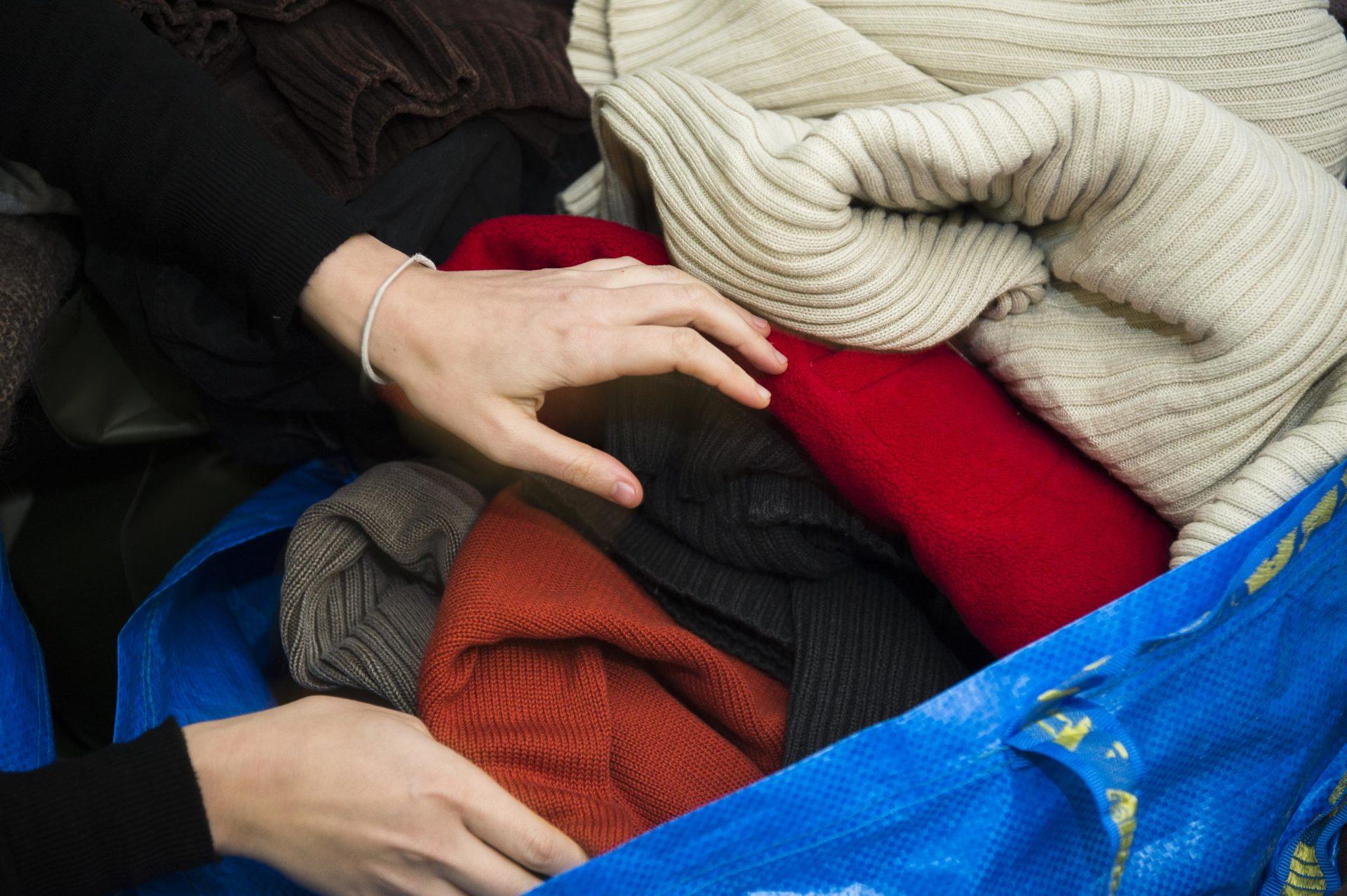 2 mains touchent des vêtements dans un sac