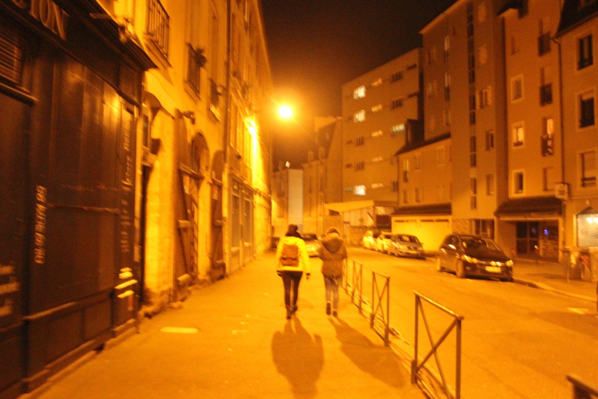 2 personnes de dos marchant dans la rue la nuit éclairées pas des lampadaires