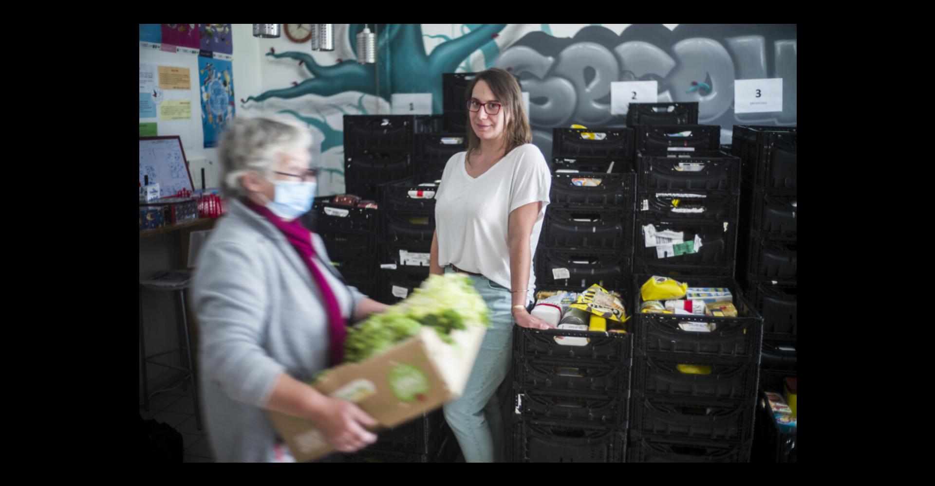 2 bénévolesdans un local de distribution de produits alimentaires, l'une posant debout, l'autre transportant une caisse de salade