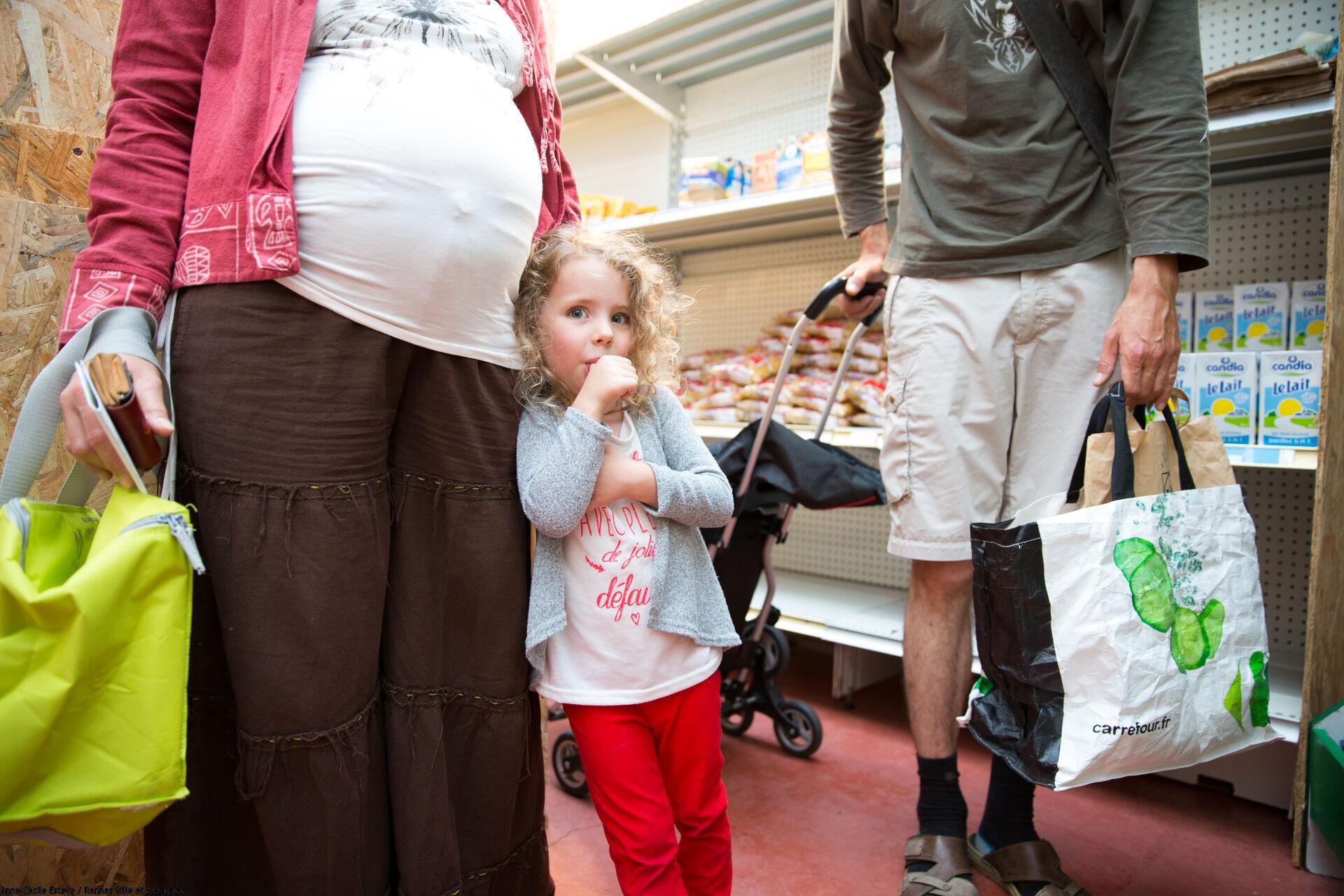 Une petite fille suce son pouce et une femme enceinte