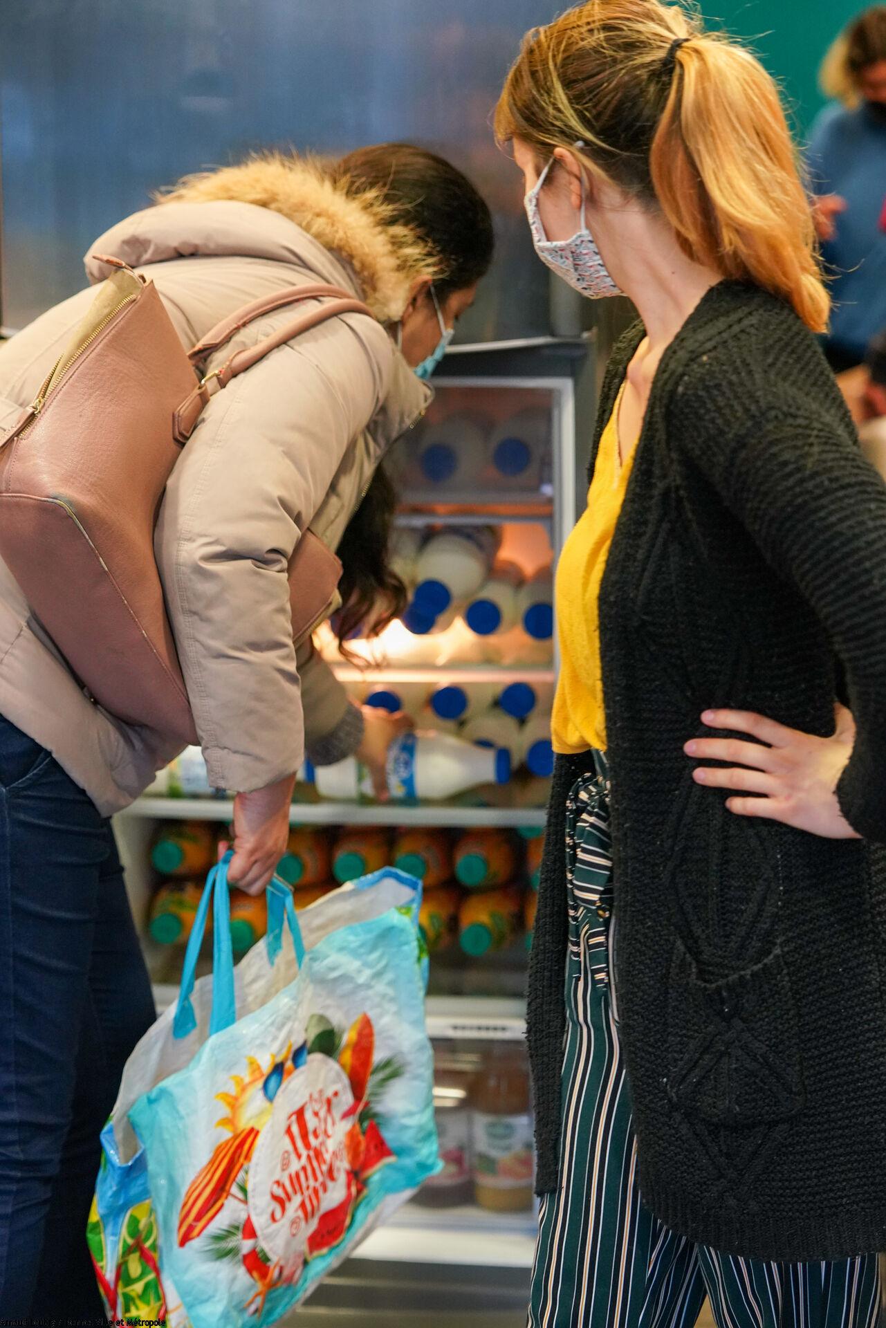 Une femme qui prend un litre de lait dans un réfrigérateur et une autre femme qui la regarde