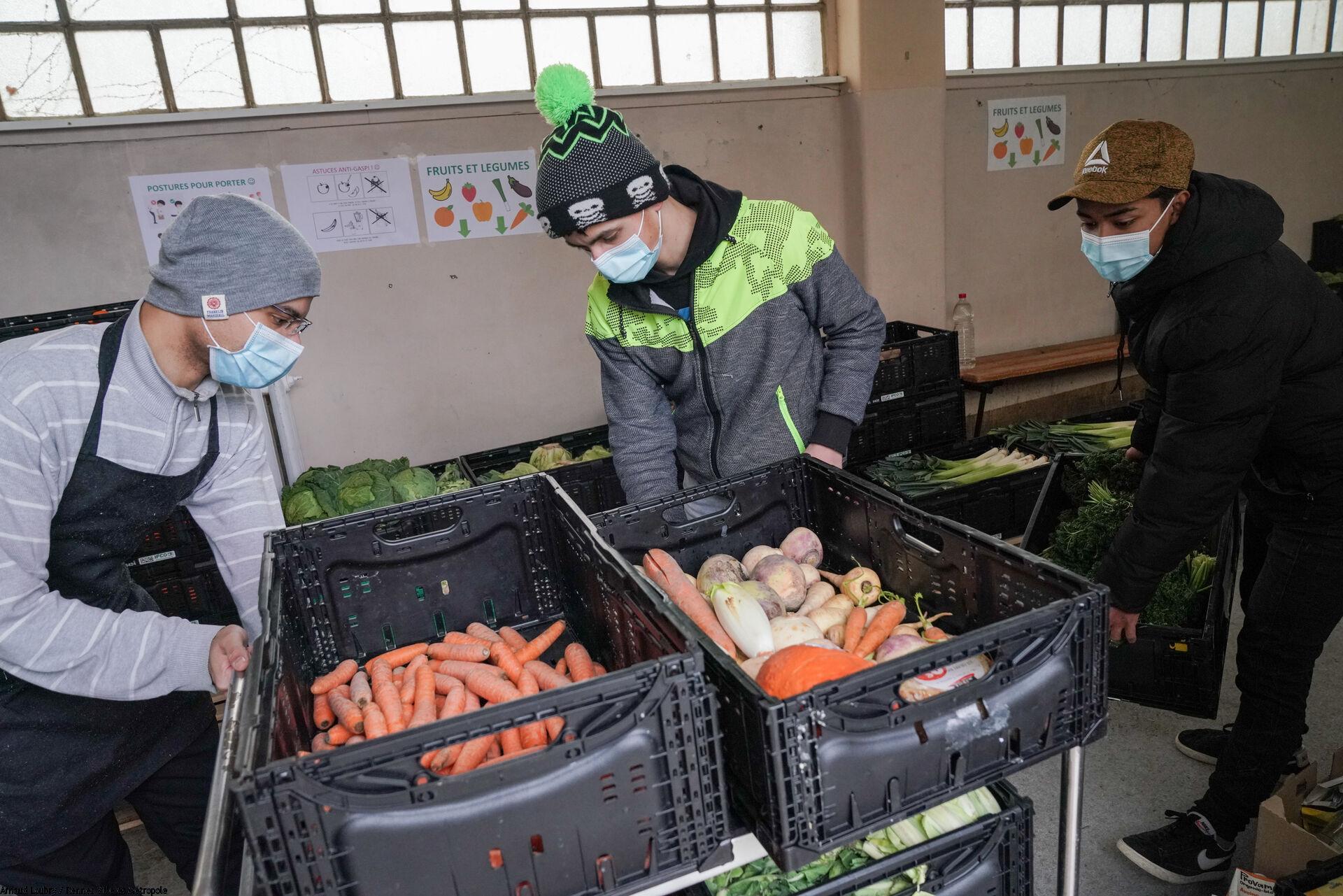 Bénévoles en train de charger des caisses d'aliments sur un charriot