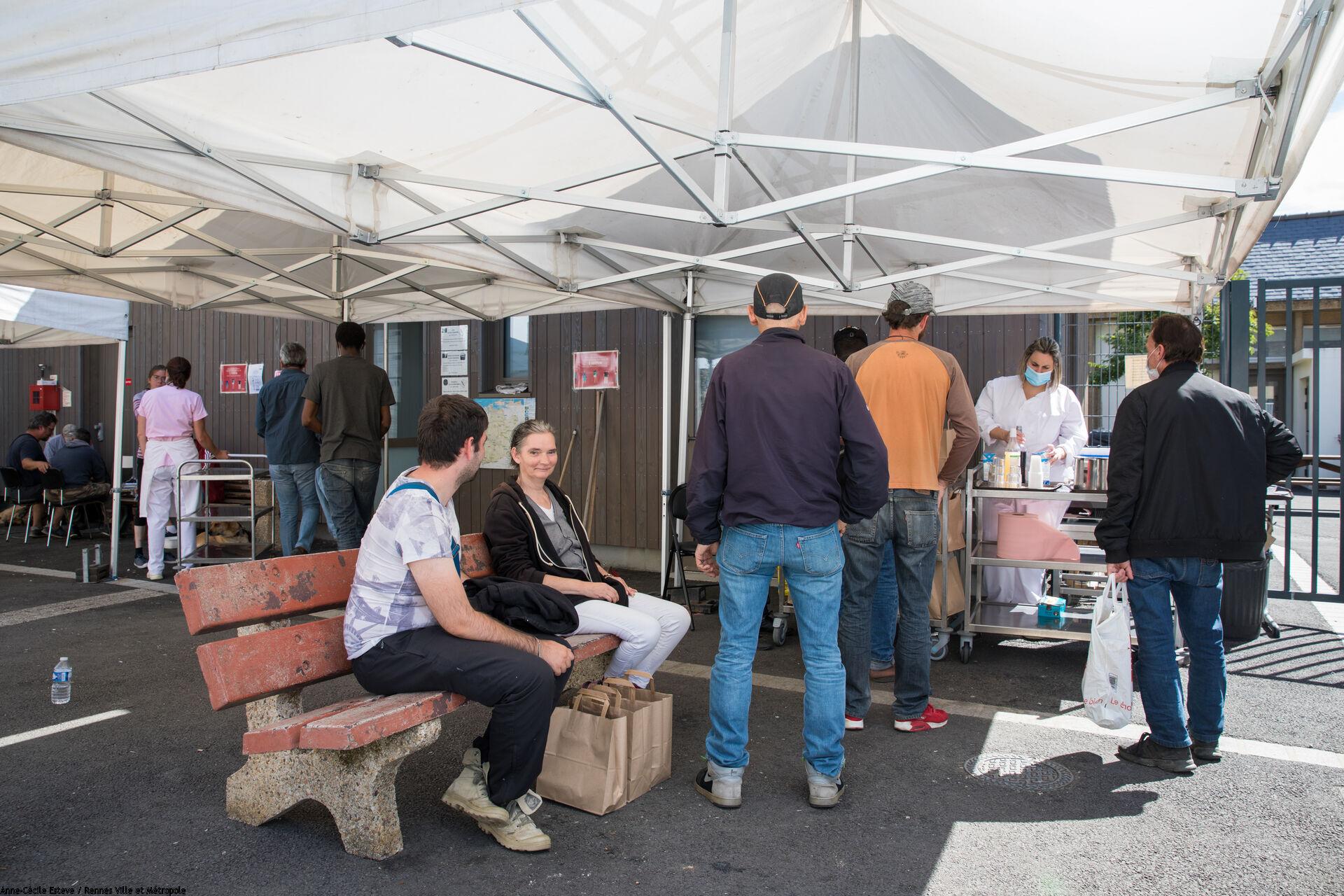 Distribution de boissons par un cantinière à des personnes sans-abri faisant la queue